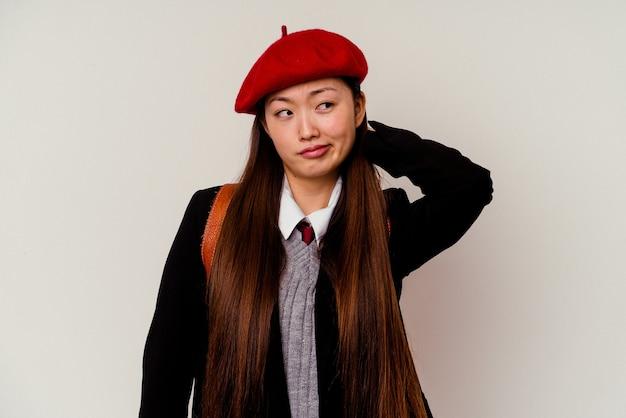 Młoda chinka ubrana w mundurek szkolny na białym, dotykając tyłu głowy, myśląc i dokonując wyboru.