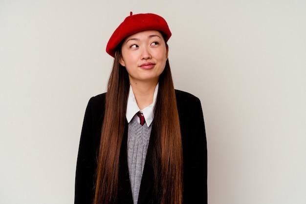 Młoda chinka ubrana w mundurek szkolny na białym tle marzy o osiągnięciu celów i zamierzeń