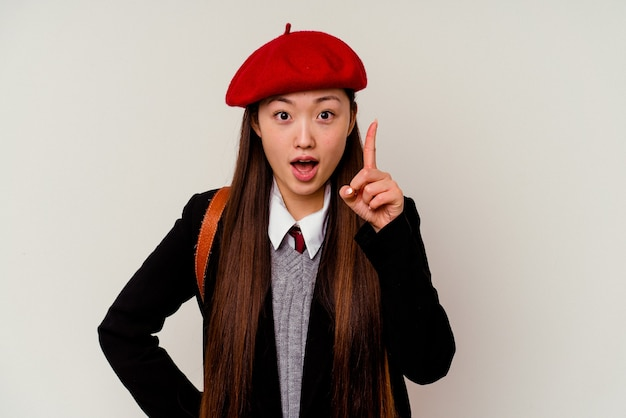 Młoda chinka ubrana w mundurek szkolny na białym tle na białej ścianie ma pomysł