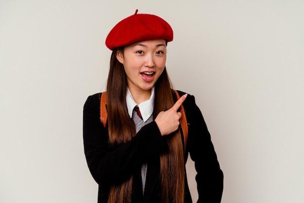 Młoda chinka ubrana w mundurek szkolny na białym tle uśmiecha się i wskazuje na bok, pokazując coś w pustym miejscu.