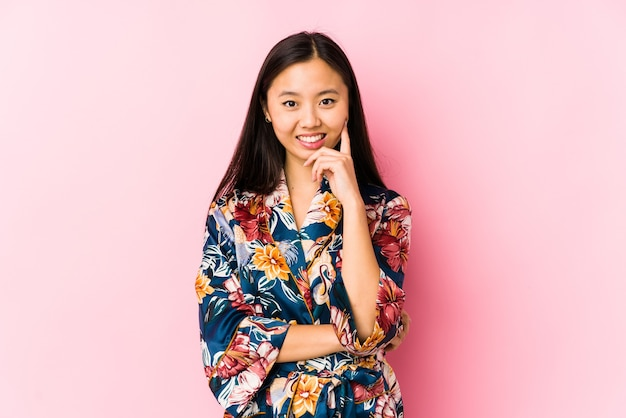 Młoda chinka ubrana w piżamę kimono na białym tle uśmiechnięty szczęśliwy i pewny siebie, dotykając brodą ręką.