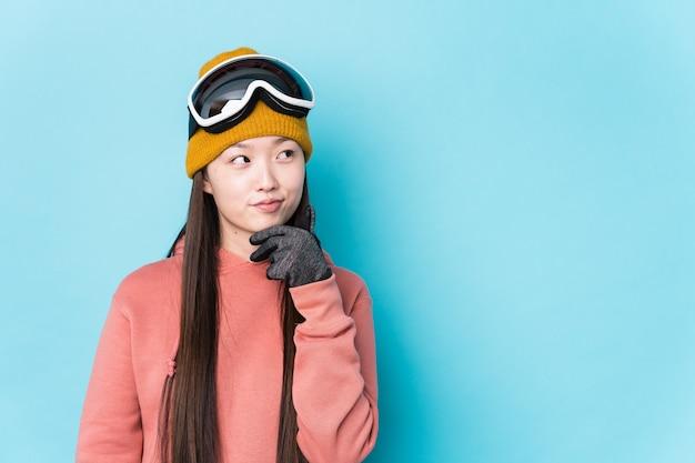 Młoda chinka ubrana w stroje narciarskie na białym tle patrząc w bok z wątpliwym i sceptycznym wyrazem twarzy.