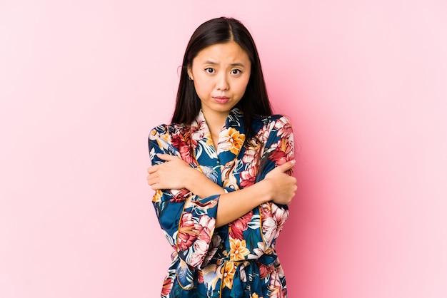 Młoda chinka w piżamie kimono na białym tle będzie zimno z powodu niskiej temperatury lub choroby.
