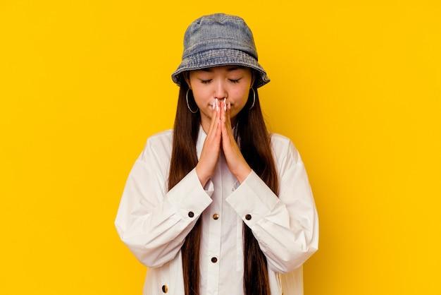 Młoda chinka wyizolowana na żółtym tle modląca się, okazująca oddanie, osoba religijna szukająca boskiej inspiracji.