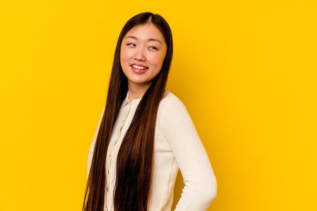 Młoda chinka wyizolowana na żółtym tle śmieje się radośnie i bawi się trzymając ręce na brzuchu.