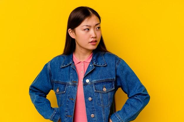 Młoda chinka wyizolowana na żółtym tle wygląda z boku uśmiechnięta, wesoła i przyjemna.