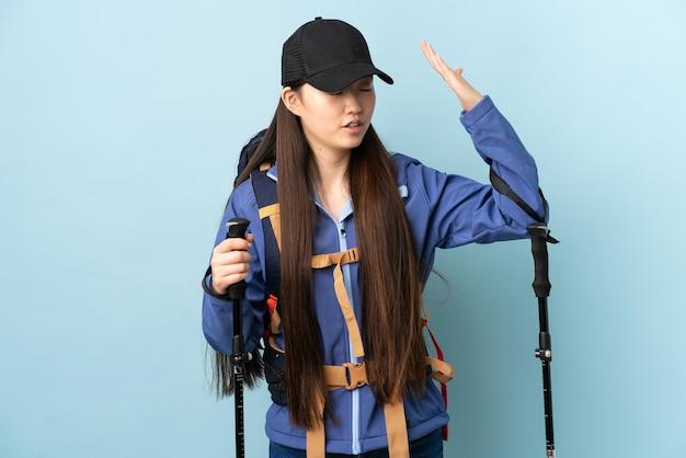 Młoda chinka z plecakiem i kijkami trekkingowymi na białym tle niebieski z wyrazem zmęczenia i choroby