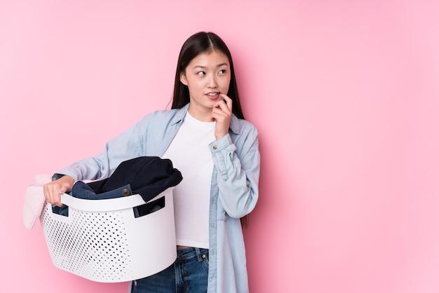 Młoda chinka zbiera brudne ubrania na białym tle zrelaksowany myślenie o czymś, patrząc na przestrzeń kopii.