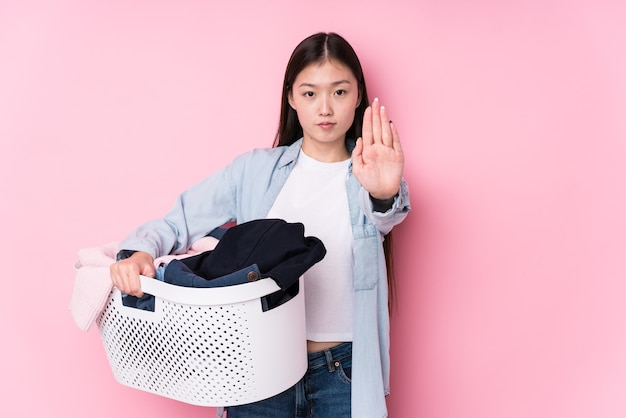 Młoda chinka zbierając brudne ubrania na białym tle stojąc z wyciągniętą ręką pokazując znak stopu, uniemożliwiając ci.