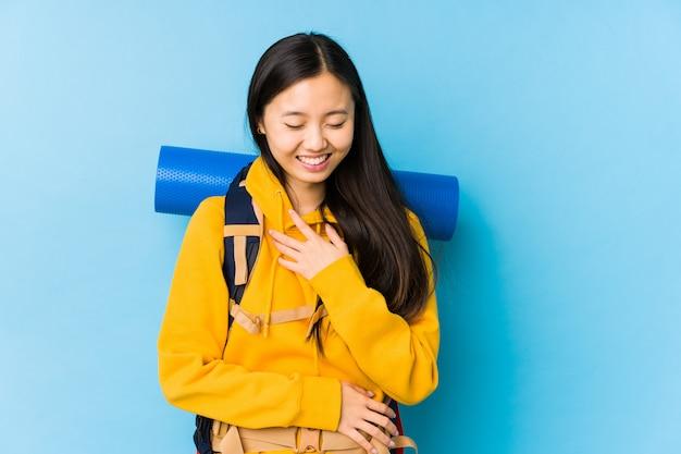 Młoda chińska backpacker kobieta odizolowywająca śmia się szczęśliwie i ma zabawę trzyma ręki na brzuchu.