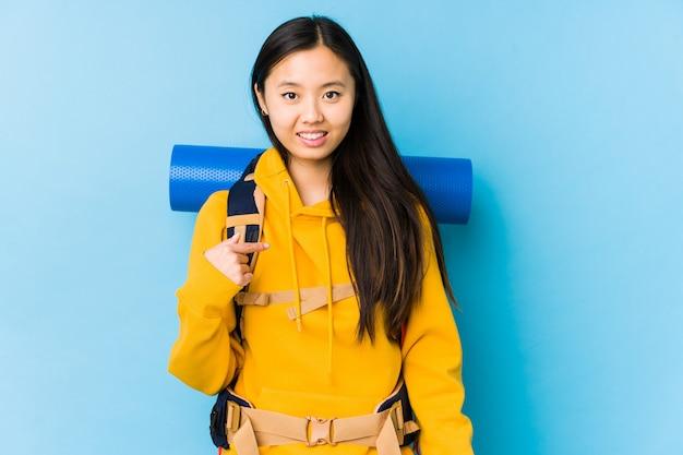 Młoda chińska backpacker kobieta odizolowywał osoby wskazuje ręcznie koszulową kopii przestrzeń, dumny i ufny