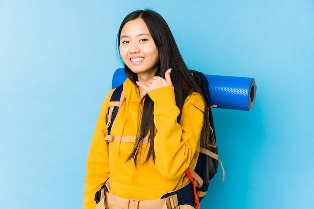 Młoda chińska backpacker kobieta odizolowywał pokazywać telefonu komórkowego wezwania gest z palcami.
