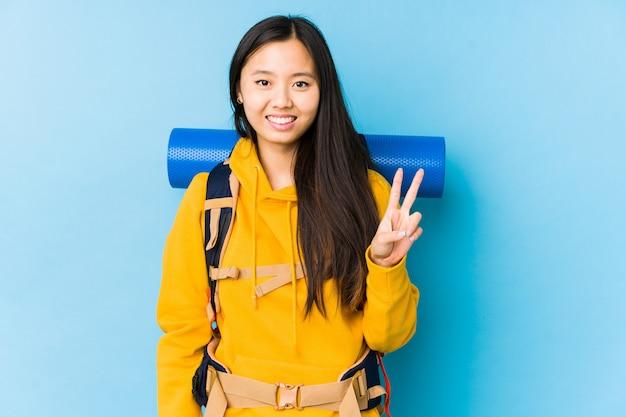 Młoda chińska backpacker kobieta odizolowywał pokazywać zwycięstwo znaka i ono uśmiecha się szeroko.