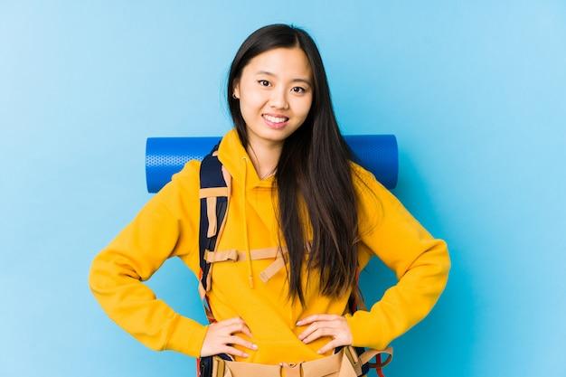 Młoda chińska backpacker kobieta odizolowywał ufne utrzymuje ręki na biodrach.