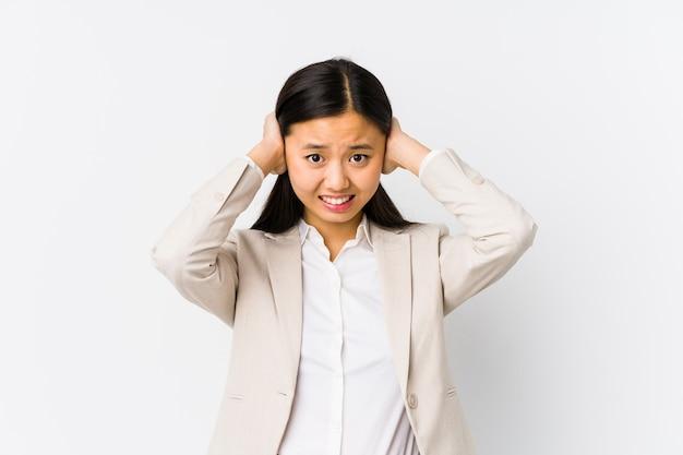 Młoda chińska biznesowa kobieta odizolowywał nakrywkowych ucho z rękami próbuje nie słuchać zbyt głośnego dźwięku.