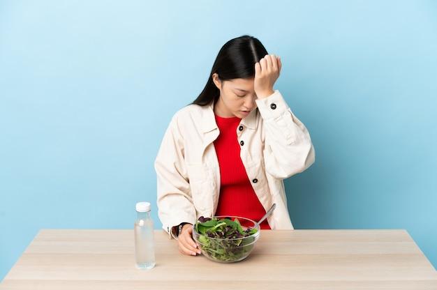 Młoda chińska dziewczyna je sałatkę z bólem głowy