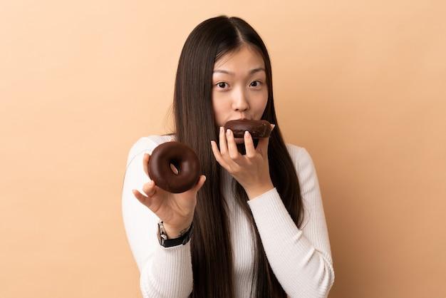 Młoda chińska dziewczyna na białym tle trzyma pączek
