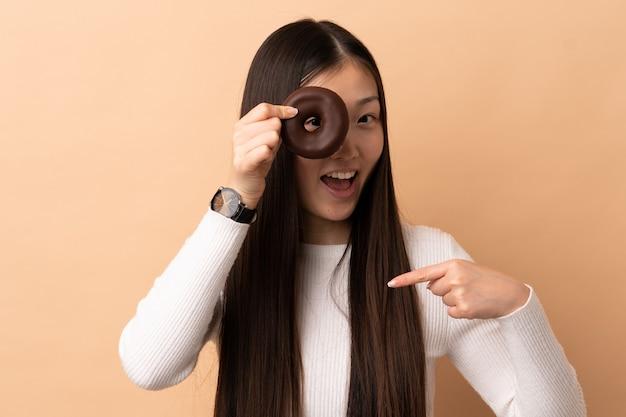 Młoda chińska dziewczyna na białym tle trzyma pączka i szczęśliwa