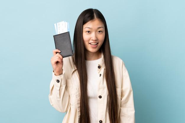 Młoda chińska dziewczyna na odosobnionym tle szczęśliwa na wakacjach z paszportem i biletami lotniczymi