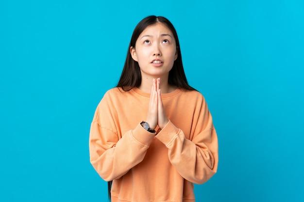 Młoda chińska dziewczyna nad odosobnioną błękit ścianą trzyma palmy wpólnie
