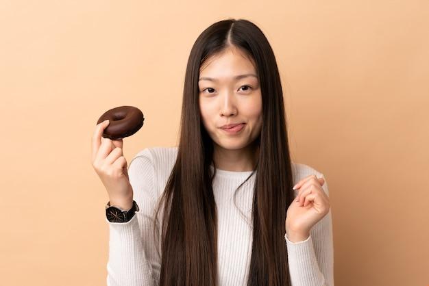 Młoda chińska dziewczyna nad trzymaniem pączka