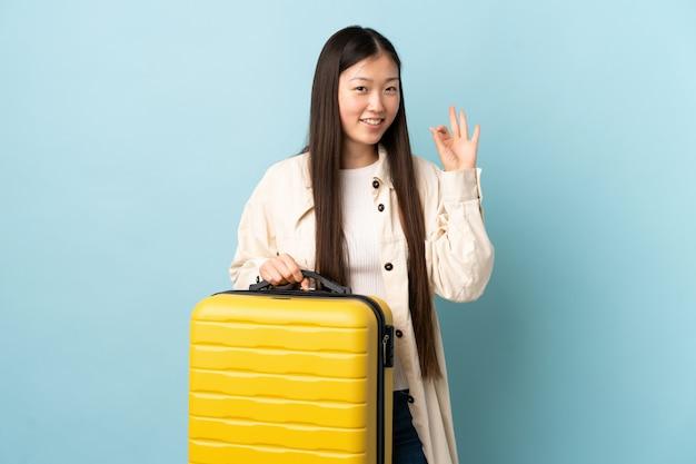 Młoda chińska dziewczyna odizolowywająca nad w wakacje z podróży walizką i robić ok znakowi