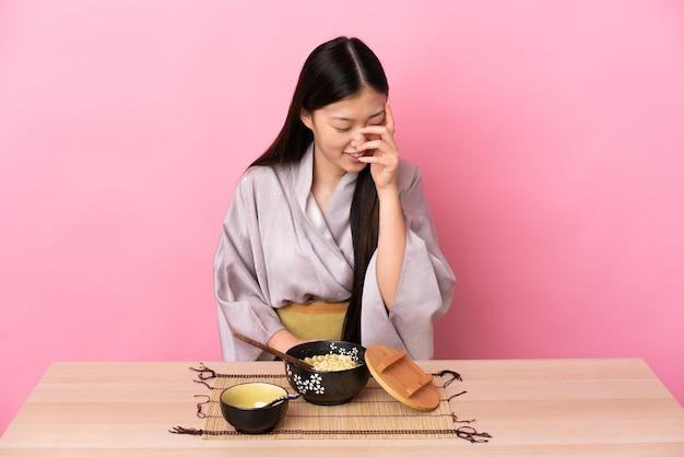 Młoda chińska dziewczyna ubrana w kimono i jedzenie makaronu śmiejąc się