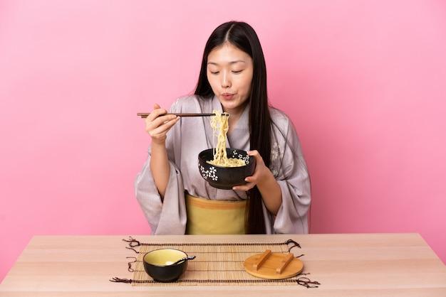 Młoda chińska dziewczyna ubrana w kimono i jedzenie makaronu w tabeli na różowo