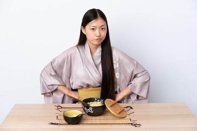 Młoda chińska dziewczyna ubrana w kimono i jedzenie makaronu zły