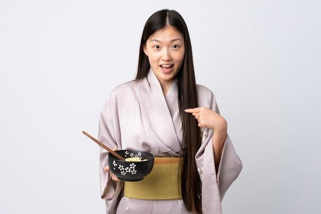 Młoda chińska dziewczyna ubrana w kimono na białym tle z wyrazem twarzy zaskoczenia, trzymając miskę makaronu z pałeczkami
