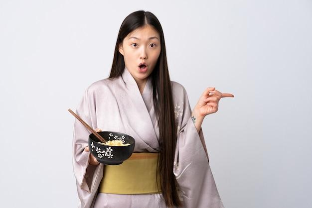 Młoda chińska dziewczyna ubrana w kimono na białym zaskoczona i wskazująca bok, trzymając miskę makaronu