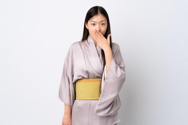 Młoda chińska dziewczyna ubrana w kimono nad szczęśliwy i uśmiechnięty obejmujący usta ręką