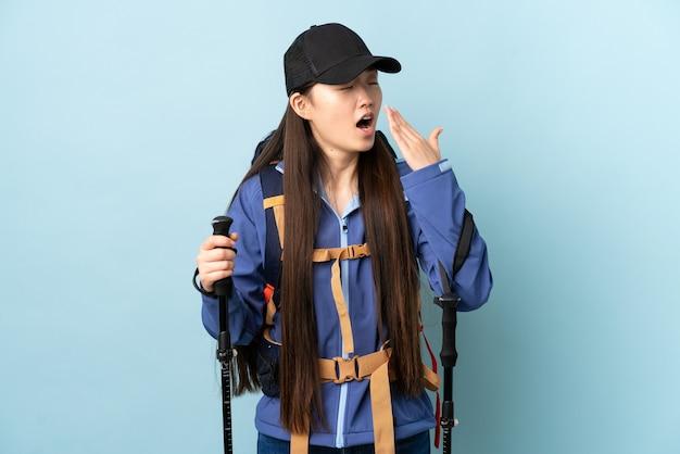 Młoda chińska dziewczyna z plecakiem i kijkami trekkingowymi nad izolowaną niebieską ścianą ziewanie i obejmowanie ręką szeroko otwarte usta