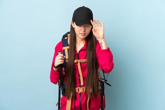 Młoda chińska dziewczyna z plecakiem i kijkami trekkingowymi nad odizolowaną niebieską ścianą z wyrazem zmęczenia i choroby