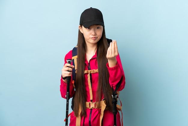 Młoda chińska dziewczyna z plecakiem i trekking słupami nad odosobnioną błękit ścianą robi włoskiemu gestowi