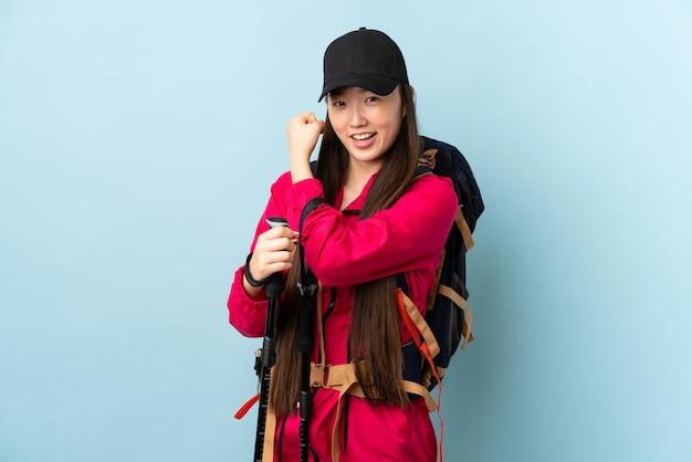 Młoda chińska dziewczyna z plecakiem i trekkingowymi słupami nad odosobnioną błękit ścianą robi silnemu gestowi