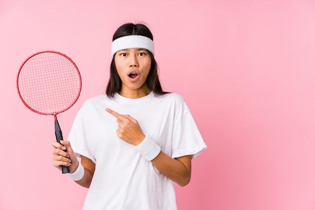 Młoda chińska kobieta bawić się badminton w różowym tle wskazuje strona