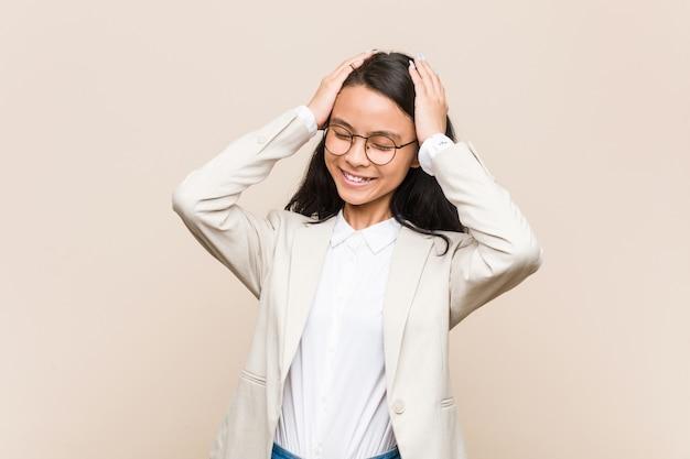 Młoda chińska kobieta biznesu śmieje się radośnie trzymając ręce na głowie. koncepcja szczęścia.