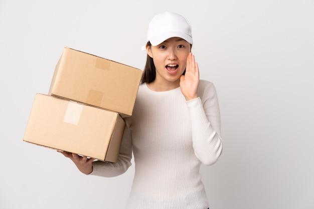 Młoda chińska kobieta dostawy na pojedyncze białe ściany krzycząc z szeroko otwartymi ustami
