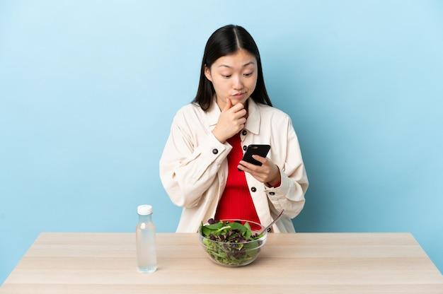 Młoda chińska kobieta je sałatkowego główkowanie i wysyła wiadomość