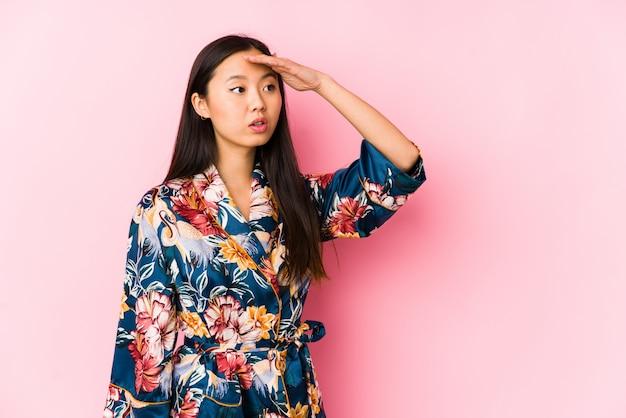 Młoda chińska kobieta jest ubranym kimonową piżamę odizolowywał patrzeć daleki utrzymuje rękę na czole.