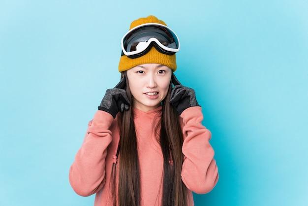 Młoda chińska kobieta jest ubranym nart ubrania odizolowywał nakrywkowych ucho z rękami.