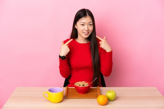 Młoda chińska kobieta ma śniadanie w stole daje aprobata gestowi