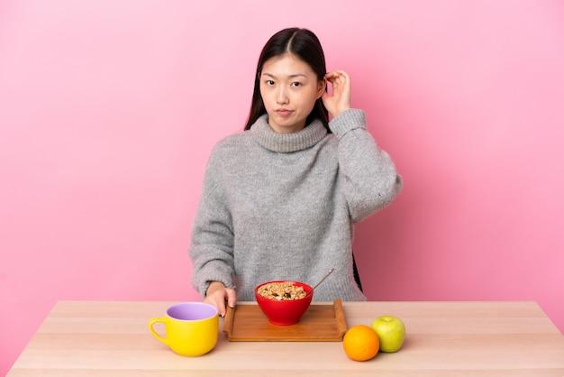 Młoda chińska kobieta ma śniadanie w stole ma wątpliwości