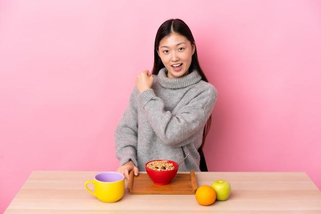 Młoda chińska kobieta ma śniadanie w stole świętuje zwycięstwo