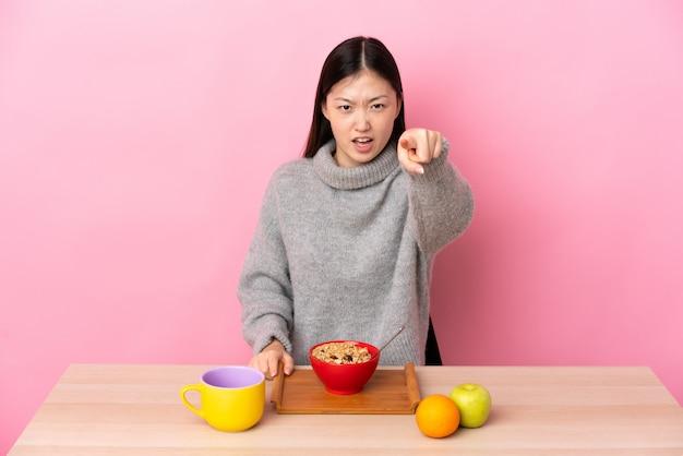 Młoda chińska kobieta ma śniadanie w stole udaremniającym i wskazuje przód