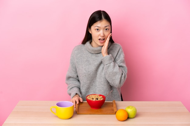 Młoda chińska kobieta ma śniadanie w stole z niespodzianką i zszokowanym wyrazem twarzy