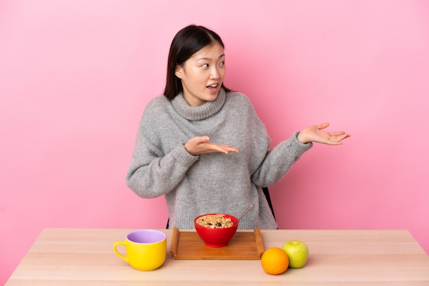 Młoda chińska kobieta ma śniadanie w stole z niespodzianki wyrażeniem podczas gdy patrzejący stronę