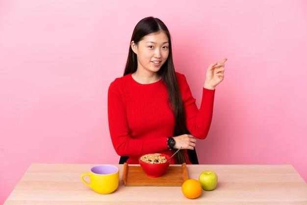 Młoda chińska kobieta ma śniadanie w stołowym wskazuje palcu strona
