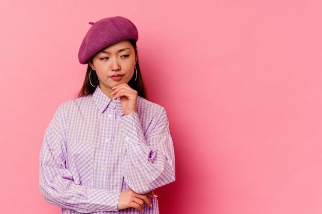 Młoda chińska kobieta na białym tle na różowym tle patrząc z boku z wyrazem wątpliwości i sceptyczny.